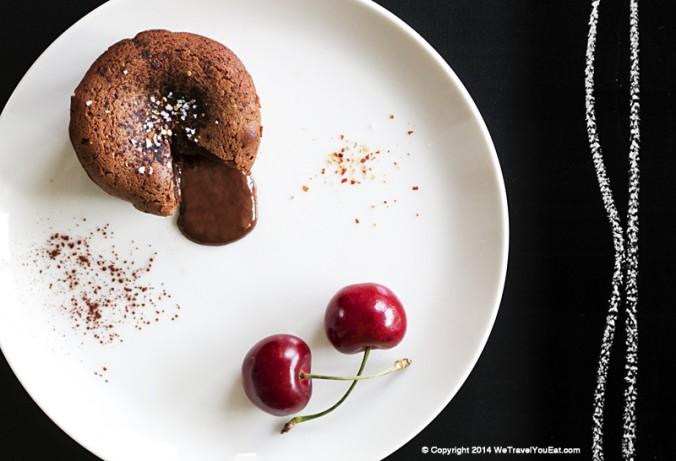 coulant au chocolat, vanille et piment d'espelette présenté avec des cerises.